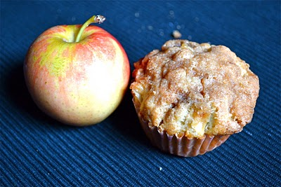 An apple cinnamon muffin with crumb topping next to a honeycrisp apple.