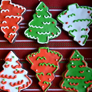 Chocolate sugar cookies shaped like Christmas trees in red, white and green royal icing.