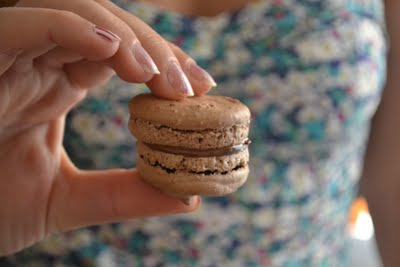 A hand holding a chocolate macaron with nutella filling.