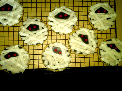 Sugar cookies decorated like mummies on a cooling rack.