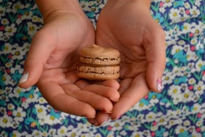 Two hands holding a chocolate macaron with nutella filling.