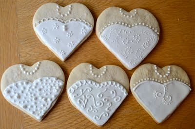Five heart shaped wedding dress sugar cookies on a wooden table.