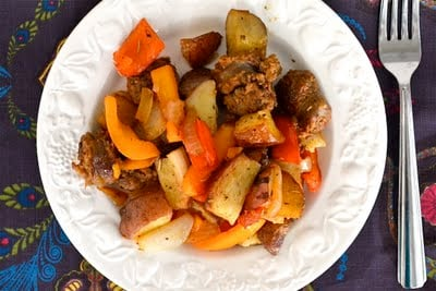 Sausage, potatoes, and bell peppers on a white plate with a fork next to it.