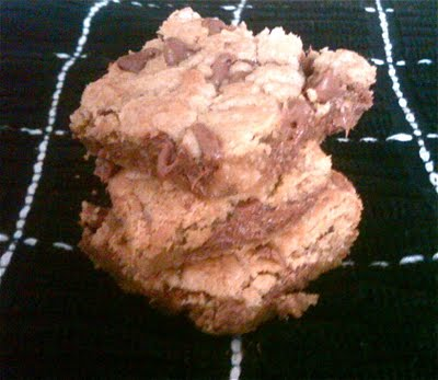 A stack of three chocolate chip cookies bars on a black and white napkin.
