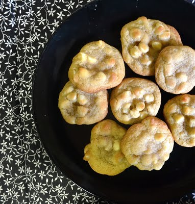 White chocolate macadamia nut cookies on a black plate with black and white floral napkin.