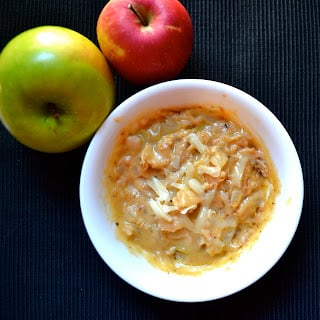 A bowl of apple chicken chili topped with cheese with apples on the side.