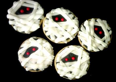 Five sugar cookies decorated like mummies.