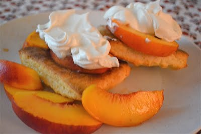 Peach shortcake topped with whipped cream on a white plate.