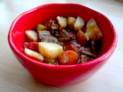 A bowl of beef stew with potatoes, carrots and celery in a red bowl.