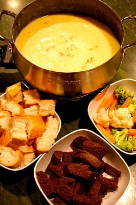 A fondue pot with swiss cheese fondue, two baskets of gluten-free bread, and a bowl of carrots, broccoli and cauliflower.